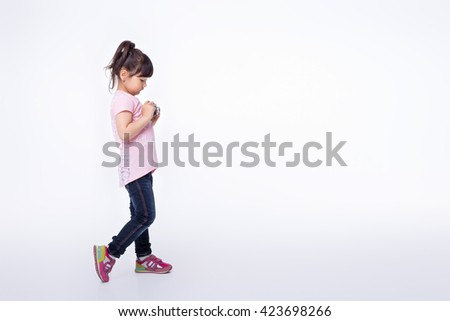 cute little girl holding an old camera. child is an old camera. training - stock photo