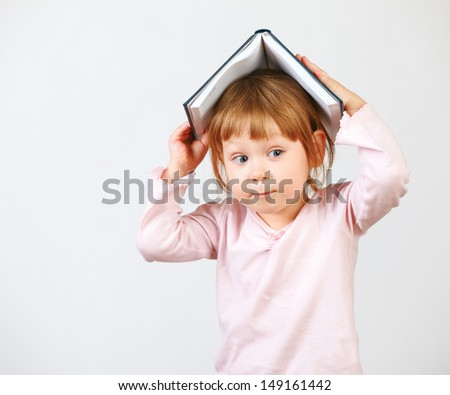 Cute little girl holding book on head. Isolated