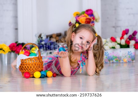cute little girl holding Easter blue egg  room is decorated with flowers