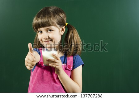 Cute little girl holding glass of milk with thumbs up,I love milk! - stock photo