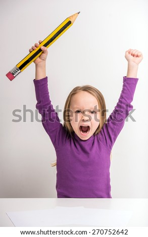 Cute little girl holding hands up with big pencil at the table on grey background. - stock photo