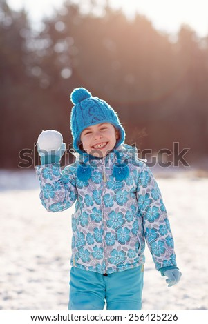Cute little girl holding up a snowball with a cheeky smile outdoors on a winter's day - stock photo