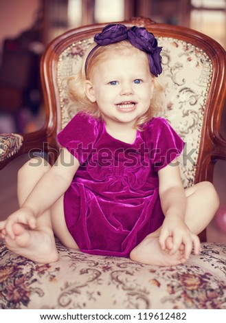 Cute little girl in a beautiful purple dress posing on a luxurious vintage chair. - stock photo