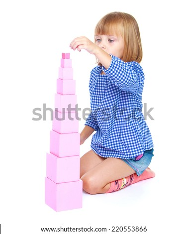 Cute little girl in a blue suit collects a pyramid, at the school Maria Montessori, isolated on white background.The concept of development of the child - stock photo