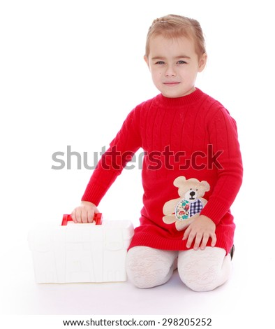 Cute little girl in a red dress sits on her knees and holding a white plastic bag , girl plays nurse -isolated on white background - stock photo