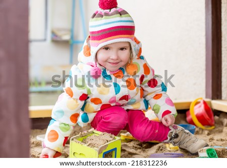 cute little girl in a sandbox  in cold weather - stock photo