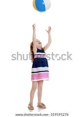 Cute little girl in a short striped dress throws in the upper hands to the ball-Isolated on white background - stock photo