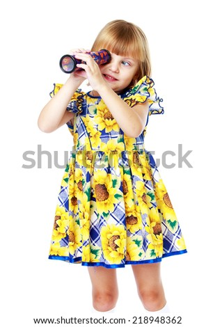 cute little girl in a yellow dress looking through a telescope isolated on a white background.Education concept happy child. - stock photo