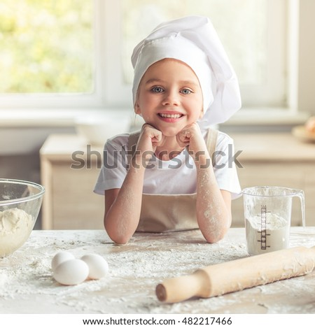 Cute little girl in apron and chef hat is looking at camera and smiling while cooking in the kitchen