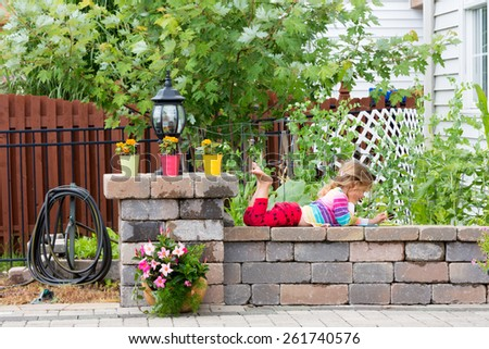 Cute little girl in bright colorful clothing lying playing on a low garden wall with her feet in the air enjoying the warm sunshine - stock photo