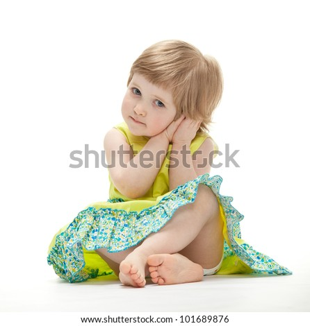 Cute little girl in colorful dress sitting on the floor, white background