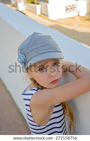 Cute little girl in denim cap in the city - stock photo