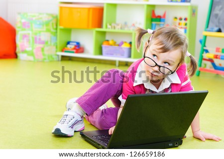 Cute little girl in glasses sitting with laptop on floor