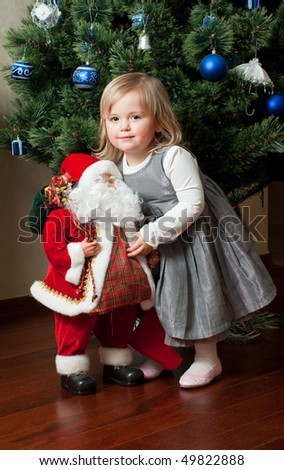 Cute little girl in gray dress with toy Santa Claus under the Christmas tree - stock photo