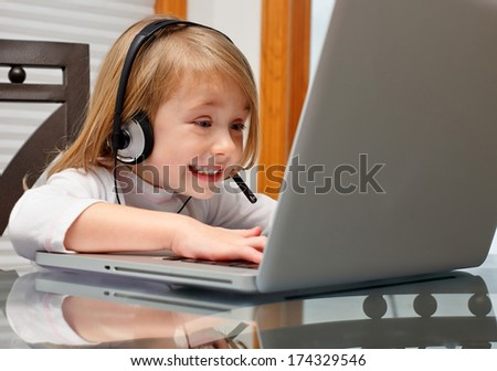 Cute little girl in headphone  sitting at the table with laptop - stock photo