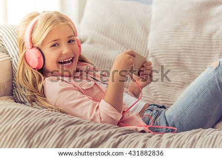 Cute little girl in headphones is using a smartphone, looking at camera and smiling while lying on the sofa at home - stock photo