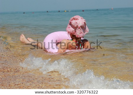 Cute little girl in panama swims in the sea with clean water with a lifeline in a sunny summer day