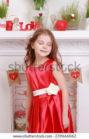 Cute little girl in red dress over valentine day background on Holiday theme - stock photo