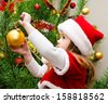 Cute little girl in santa hat decorating the christmas tree  - stock photo