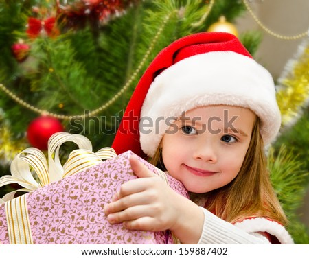 Cute little girl in santa hat with present have a christmas  - stock photo