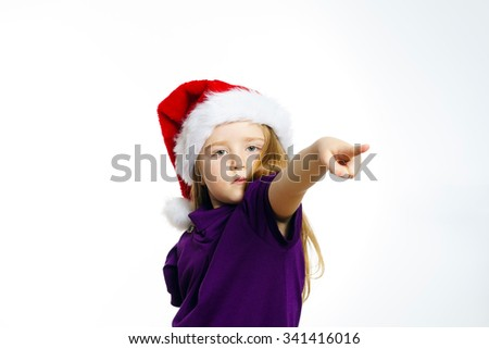 Cute little girl in santa red hat showing by hand, isolated on white