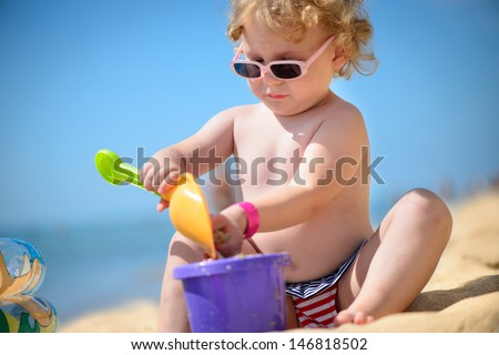 Cute little girl in sunglasses playing with sand at ocean beach