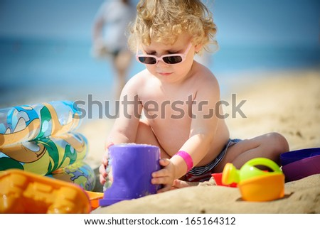 Cute little girl in sunglasses playing with sand at ocean beach - stock photo