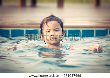 Cute little girl in swimming pool in vintage color style - stock photo