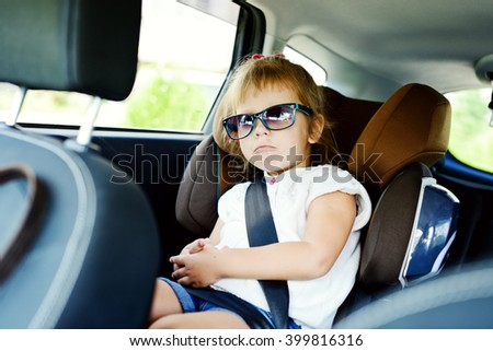 cute little girl in  the car seat - stock photo