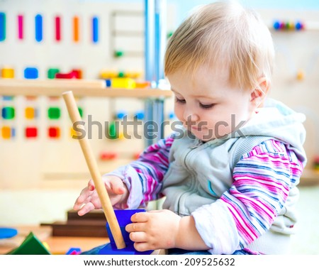 cute little girl in the classroom early development plays with numerous bright toys - stock photo