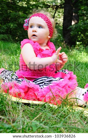 Cute little girl in the meadow in pink suit - stock photo