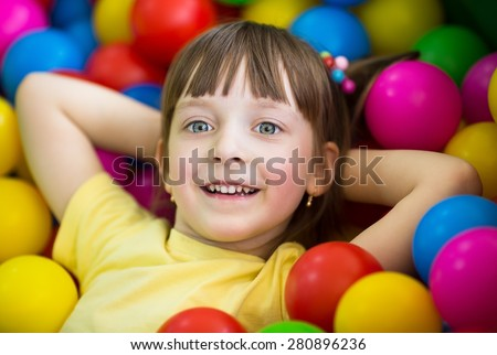 Cute little girl in the playing room with  colorful balls - stock photo