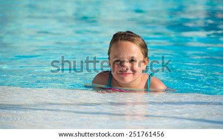 Cute little girl in the swimming pool - stock photo