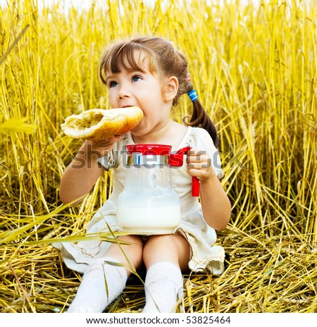 cute little girl in the wheat field eating a long loaf and drinking milk - stock photo