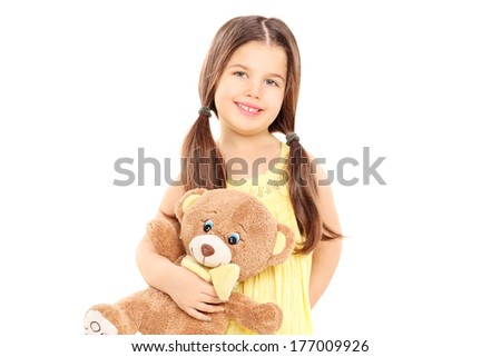 Cute little girl in yellow dress holding a teddy bear isolated on white background