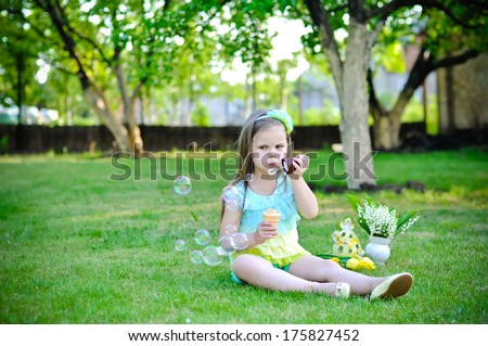 Cute little girl is blowing a soap bubbles on Easter - stock photo