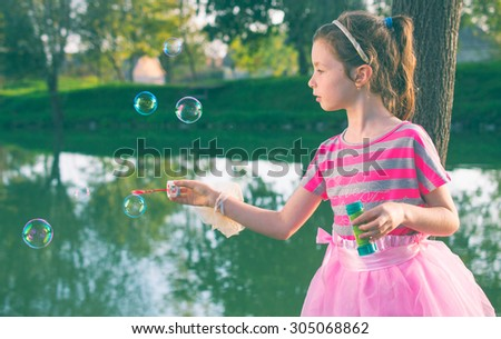 Cute little girl is blowing soap boubles - stock photo