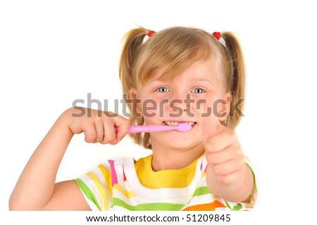 Cute little girl is brushing teeth with thumbs up