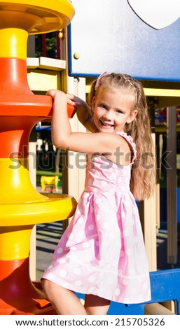 Cute little girl is climbing up on ladder in playground equipment  - stock photo