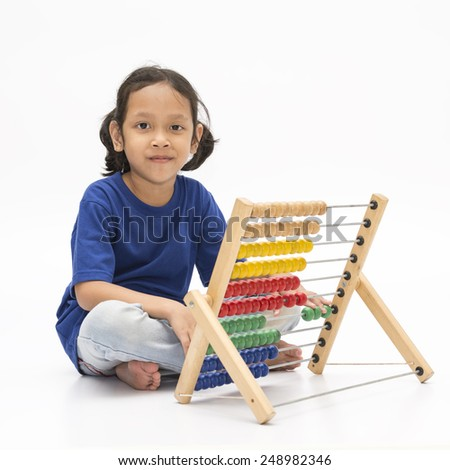 Cute little girl is counting on abacus over white background. Early education concept - stock photo
