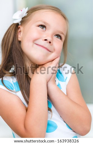 Cute little girl is daydreaming - stock photo