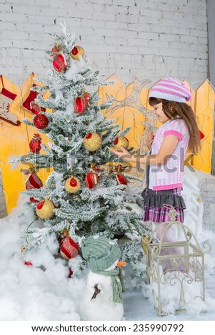 Cute little girl is  decorating the christmas tree - stock photo