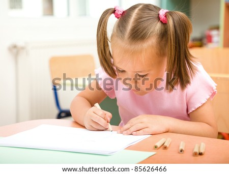 Cute little girl is drawing with color pencils in preschool