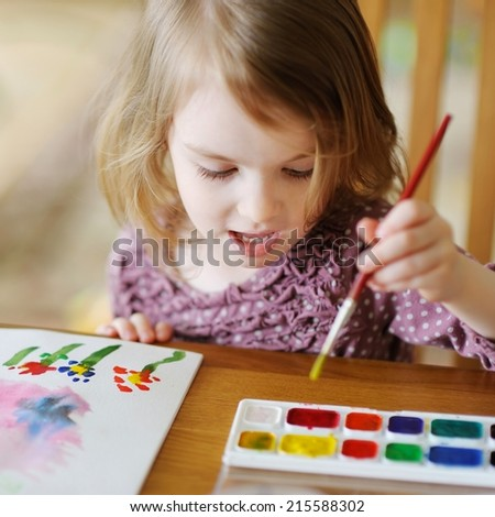 Cute little girl is drawing with paints in preschool - stock photo