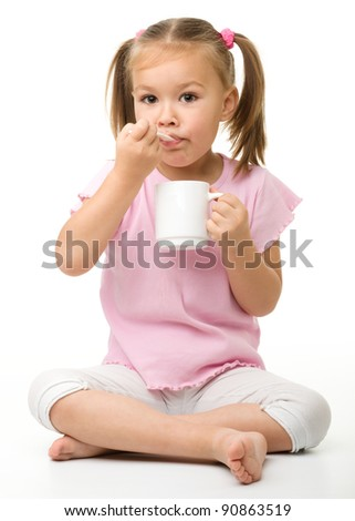 Cute little girl is eating something from cup using spoon while sitting on floor, isolated over white - stock photo