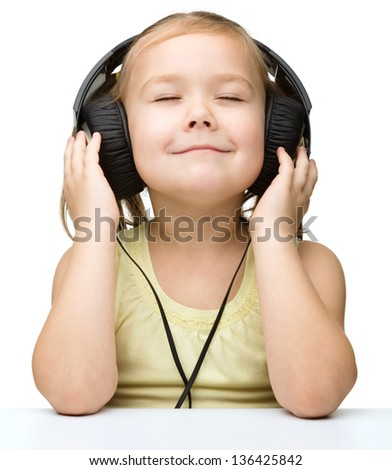 Cute little girl is enjoying music using headphones and closed her eyes, isolated over white - stock photo