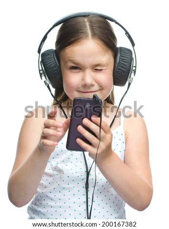 Cute little girl is enjoying music using headphones, isolated over white - stock photo