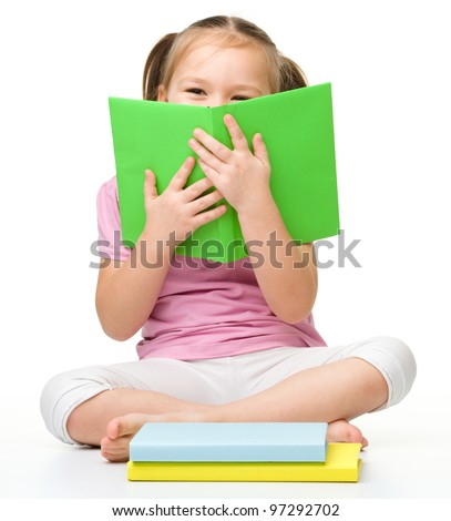 Cute little girl is hiding behind a book, isolated over white - stock photo