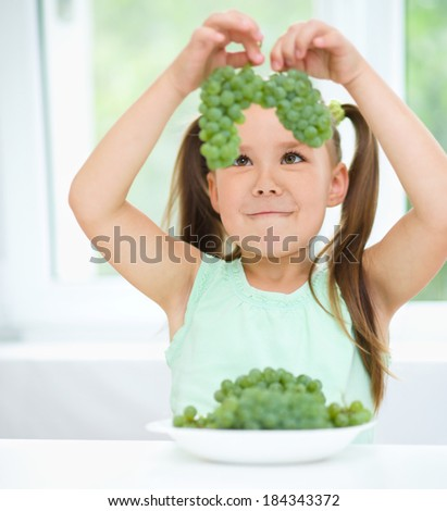 Cute little girl is looking at bunches of green grapes, isolated over white - stock photo