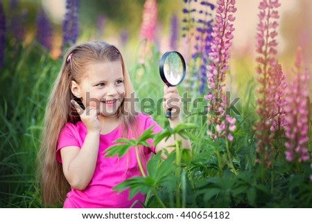 Cute little girl is looking at the flowers through magnifier, outdoor shoot - stock photo